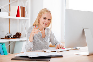 Portrait of a young smiling business woman working with computer and pointing finger at camera