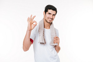 Portrait of a young smiling fitness man with towel showing okay gesture and looking at camera isolated on a white background