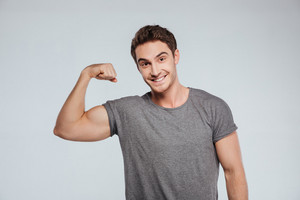 Portrait of a young smiling man with one arm up flexing his bicep isolated on the gray background