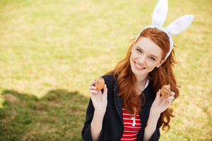 Portrait of a young smiling red head woman wearing bunny ears and showing two painted easter eggs outdoors