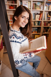 Portrait of a young smiling student reading a book at bookshelf in the library