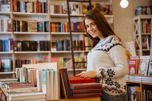 Portrait of a young smiling woman searching for a book in bookstore