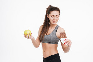 Portrait of a young sports woman looking at chocolate in her hand with an apple in her other hand isolated on a white background