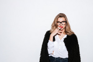 Portrait of a young stylish woman in fur coat and eyeglasses smoking cigarette and looking at camera on white background