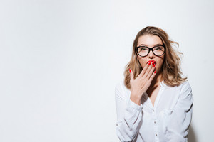 Portrait of a young surprised woman in eyeglasses looking at camera isolated on a white background