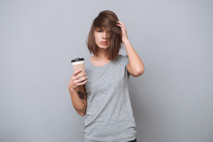 Portrait of a young tired girl with messy hair holding cup of coffee isolated on a gray background