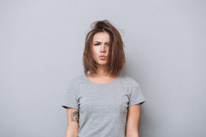 Portrait of a young upset girl in t-shirt looking at camera isolated on a gray background