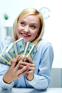 Portrait of a young woman holding roll of banknotes and enjoying