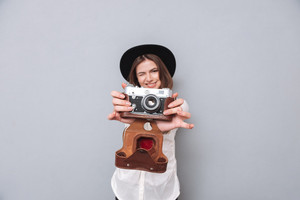 Portrait of a young woman in hat holding retro camera and taking photo, focus on camera isolated on the gray background