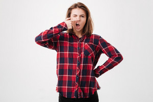 Portrait of a young woman in plaid shirt making a funny face over white background