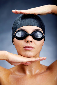 Portrait of a young woman posing in goggles and swimming cap