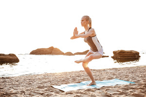 Portrait of a young woman standing in yoga pose on one leg on beach