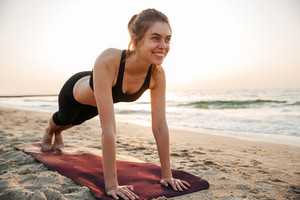 Portrait of a young woman stretching on yoga mat outdoors at the beach