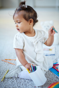 Portrait of adorable little girl with colorful pencils