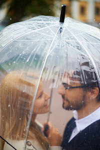 Portrait of affectionate couple under umbrella outside