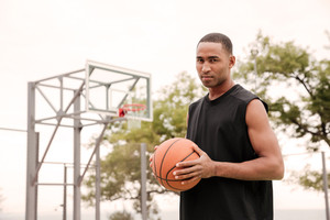 Portrait of african serious basketball player standing in the street with basketball hoop at background. Looking at camera.