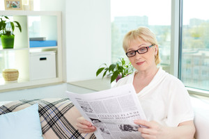 Portrait of aged woman reading newspaper at home