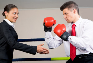 Portrait of aggressive businessman in boxing gloves fighting with positive female with her arm stretched for handshake