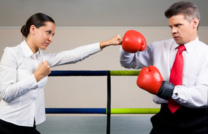 Portrait of aggressive businessman in boxing gloves fighting with serious female