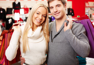 Portrait of amorous couple of shoppers looking at camera with smiles