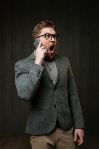 Portrait of an angry bearded man talking on the mobile phone and shouting isolated on the black wooden background