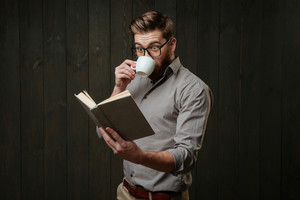 Portrait of an astonished bearded man in eyeglasses drinking coffee and looking at open book isolated on a black wooden background