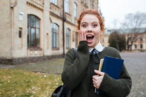 Portrait of an astonished redheaded woman student holding books outside university campus