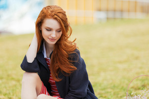 Portrait of an attractive young red head woman with long hair in park