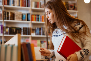 Portrait of an attractive young woman holding book in library