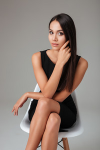 Portrait of an elegant brunette businesswoman in black dress sitting on the chair over gray background