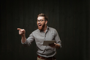 Portrait of an excited bearded man holding tablet computer and pointing finger away isolated on a black wooden background