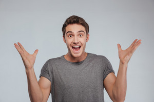 Portrait of an excited casual man standing with raised hands and looking at camera isolated on a white background