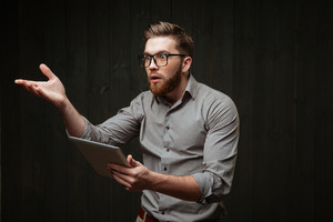 Portrait of an unsatisfied bearded man in eyeglasses holding tablet computer and gesturing isolated on a black wooden background