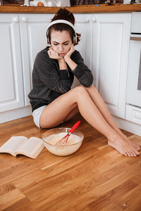 Portrait of an upset frustrated girl in headphones sitting on the kitcchen floor and reading recipe book