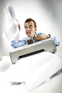 Portrait of annoyed businessman holding papers printed by scanner