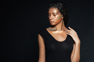 Portrait of attractive african american young woman with fashion makeup over black background