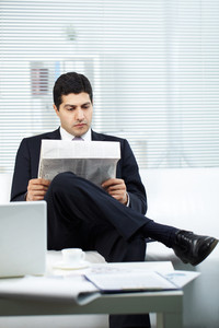 Portrait of attractive businessman in suit reading paper in office