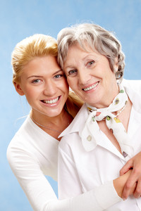 Portrait of attractive daughter hugging mother on a blue background