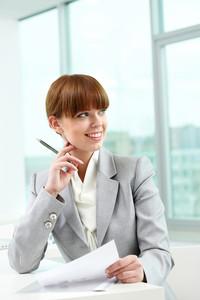 Portrait of attractive office worker looking aside in office