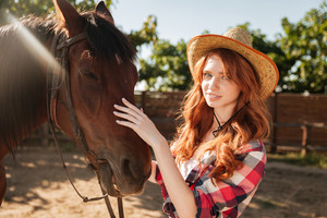 Portrait of attractive redhead young woman cowgirl in hat with her horse