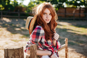 Portrait of attractive redhead young woman cowgirl standing outdoors