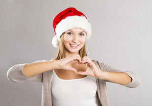Portrait of attractive woman isolated on gray, studio shot in christmas hat