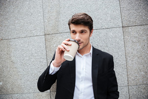 Portrait of attractive young businessman standing and drinking coffee