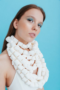 Portrait of attractive young woman in marshmallow necklace over blue background