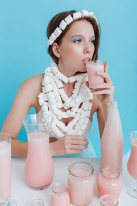 Portrait of attractive young woman with marshmallow necklace sitting and drinking juice over blue background