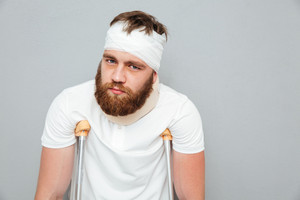 Portrait of bandaged bearded young man standing with crutches over white background