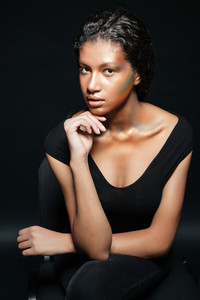 Portrait of beautiful african american young woman with stylish makeup sitting and posing on chair over black background