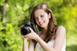 Portrait of beautiful brunette girl making photos at summer green park.