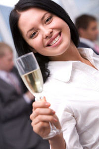 Portrait of beautiful female stretsching flute with champagne and smiling at camera