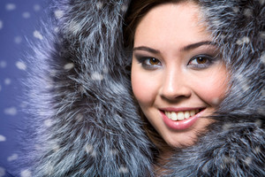 Portrait of beautiful female wearing fur cap and smiling